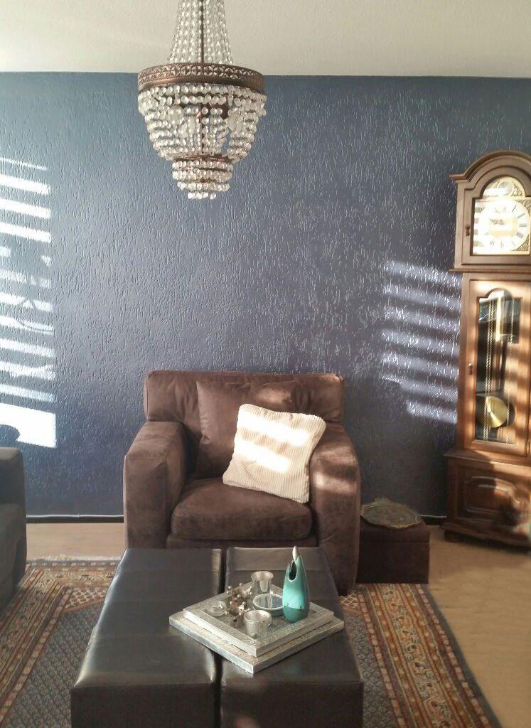 Leren fauteuil blauwe muurverf woonkamer
